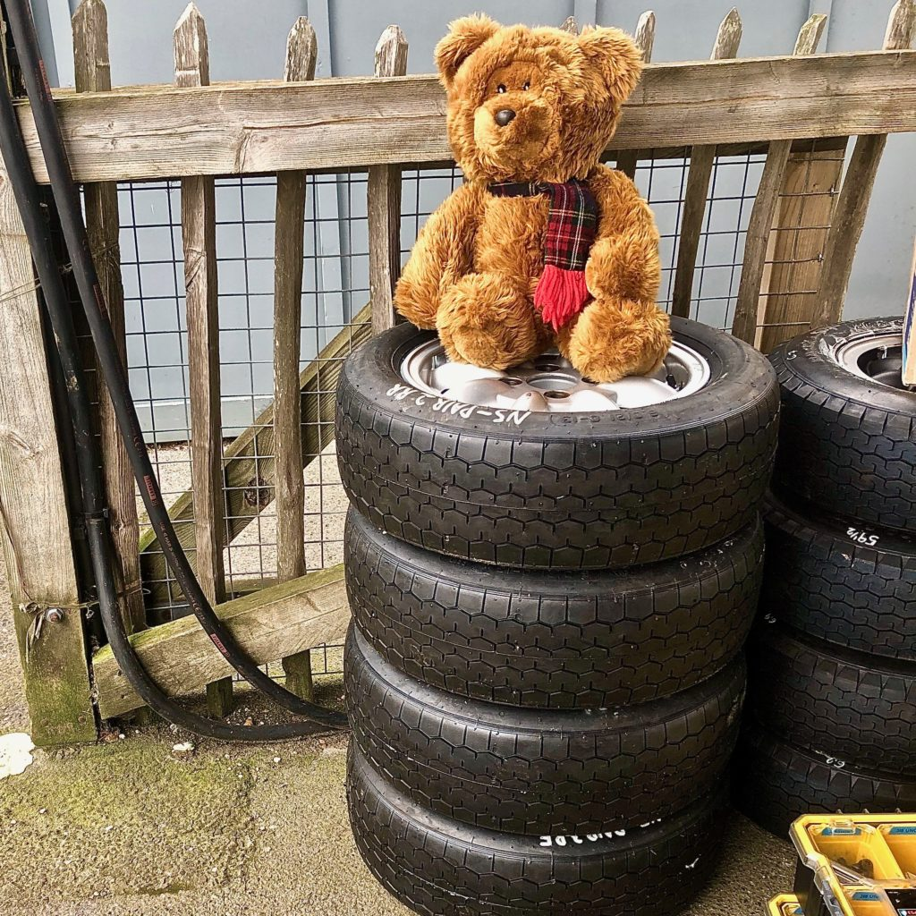 Hemel Bear sitting on a pile of tyres, belonging to Sime Racing. In the paddock resting, during practice for the 77MM at Goodwood. Photo by Marcia White for Join The World Magazine.